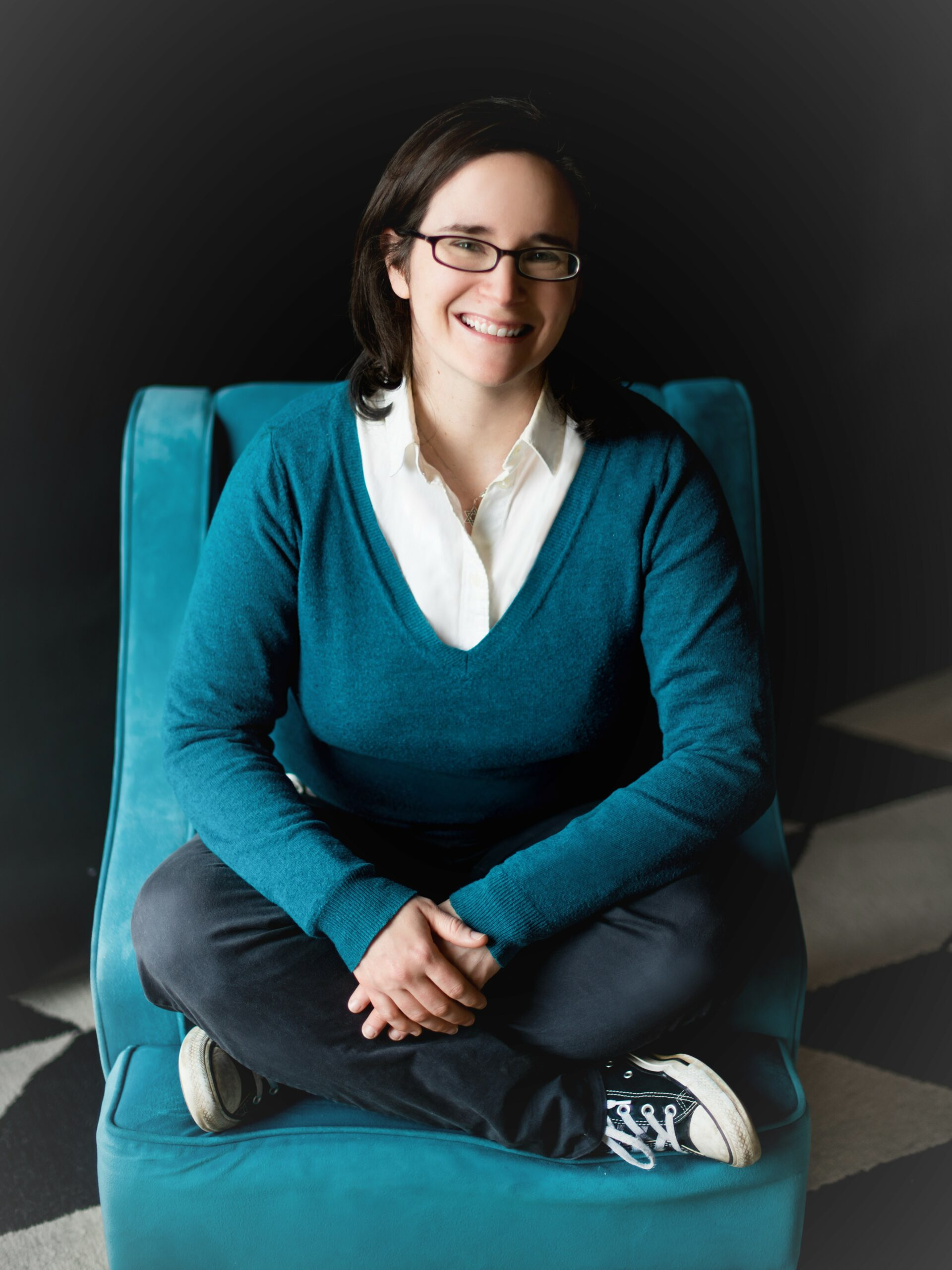 A smiling woman dressed in blue sitting cross-legged on a blue chair